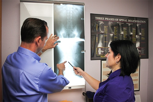 Chiropractor Fountain Valley CA Lysa Stark and Randy Stark Looking over X-Rays